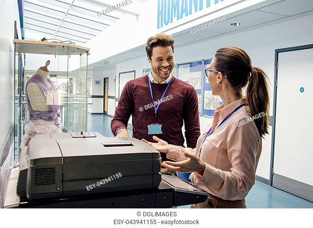 Two teachers are talking while standing at a printer in the school hall