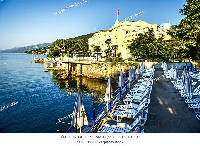 Empty sun chairs and closed umbrellas on the waterfront near the Kvarner hotel in Opatija in Croatia