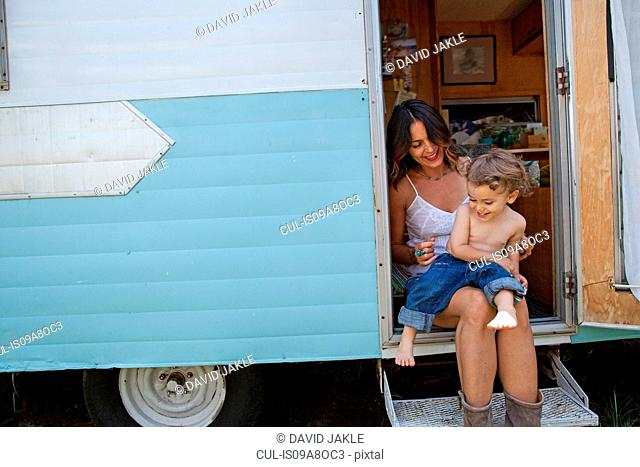 Mother and son sitting in doorway of motor home
