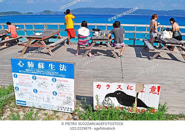 Zamami, Okinawa, Japan: tourists and signs one warning about crows-thieves at Furuzamami Beach