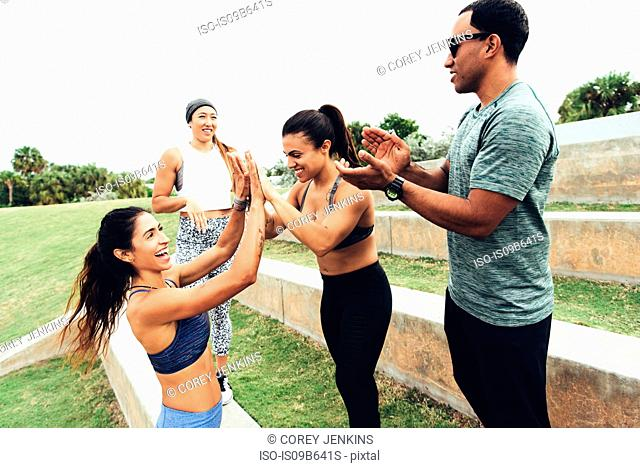 Three women celebrating workout, personal trainer clapping, Point Park, Miami Beach, Florida, USA