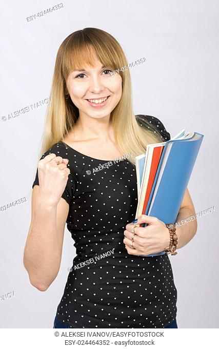 Cheerful girl with folders in hands clenching his fist in the frame smiles