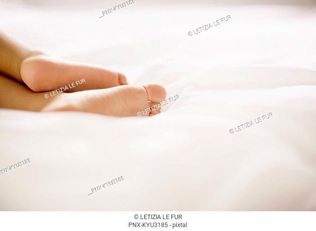 Human feet on bed