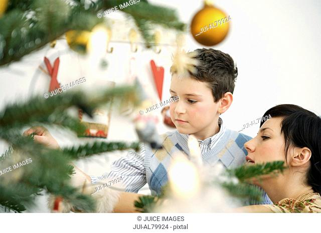 Mother and young son decorating Christmas tree