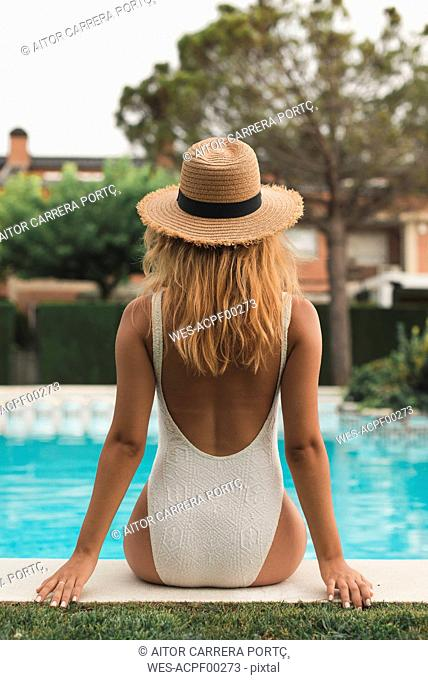Young woman with straw hat sitting at poolside, rear view