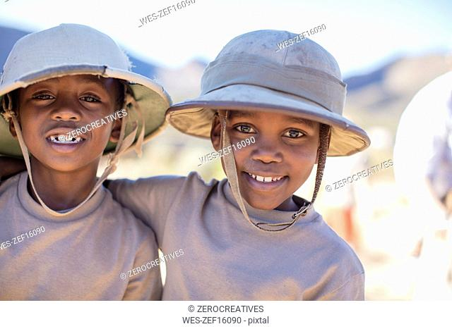 Portrait of two smiling boys embracing wearing pith helmet