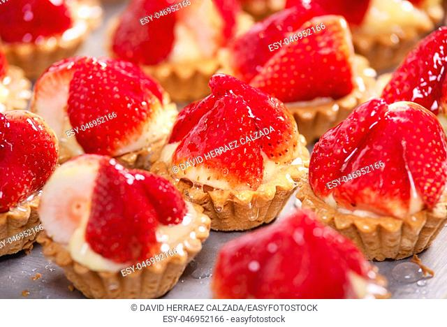 Close up of delicious tartlets with fresh strawberries and vanilla cream