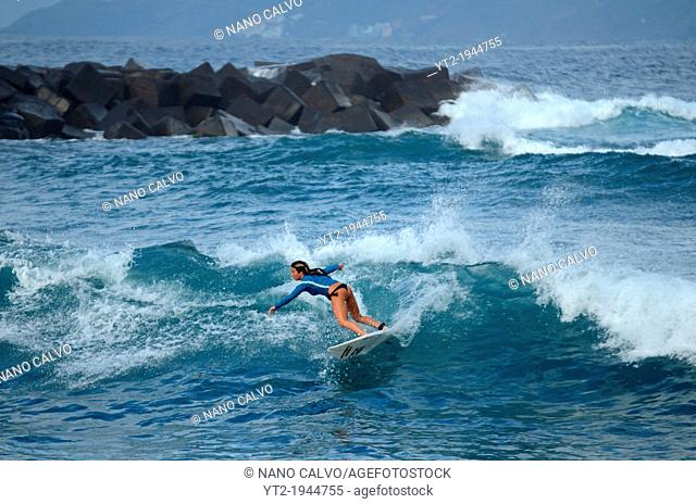 Attractive young woman surfing in Puerto de la Cruz, Tenerife