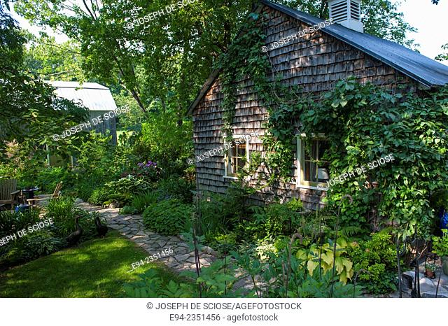 A garden and a house with cedar siding in île d'Orléans, Quebec, Canada