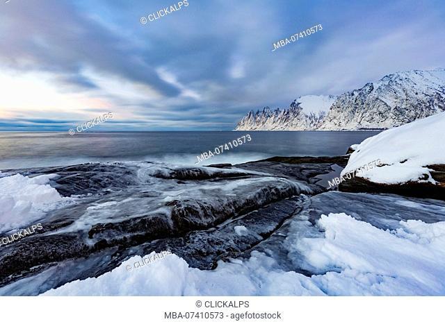 Shore of jevelens tanngard in front of okshornan peaks (devil's jaw) after sunset, senja, nordland, norway, europe