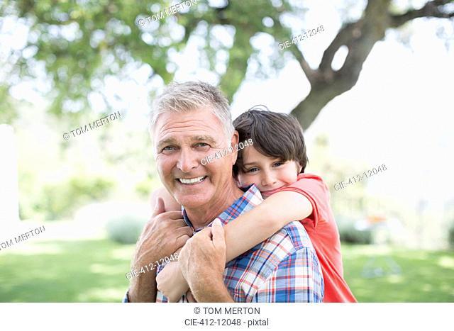 Man piggybacking grandson outdoors