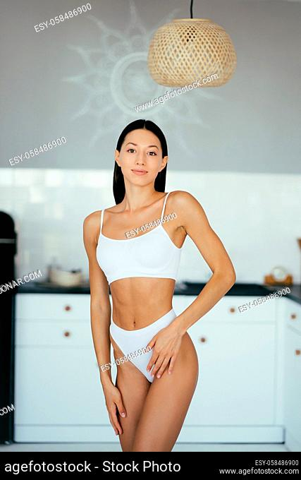 Beautiful young girl posing in lingerie in the kitchen. Fashion portrait model in kitchen