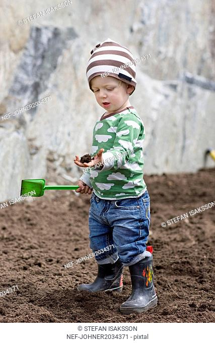 Boy digging in soil