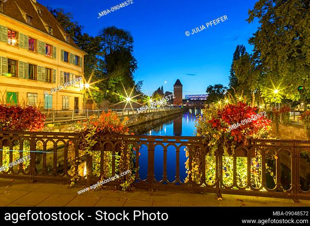 Colorful autumn canal scene in Petite France, Strasbourg, Alsace, France with flowers tracing over the balustrades of the night sky and reflection on the water