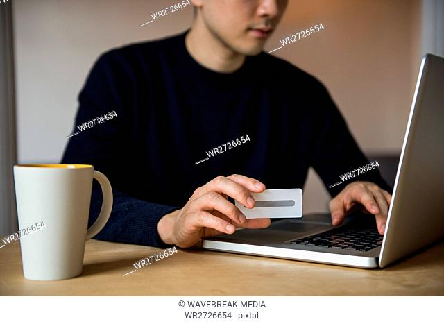 Man doing online shopping on laptop