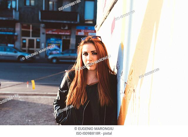 Portrait of red haired woman leaning against wall looking at camera