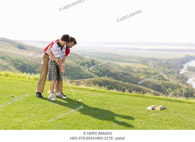 father helping pre-teen son with golf stance