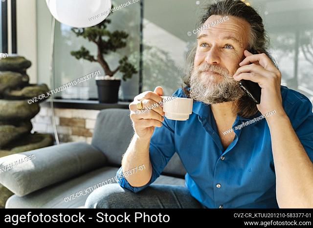 Mature man drinking a coffee and talking on the phone sitting on a sof