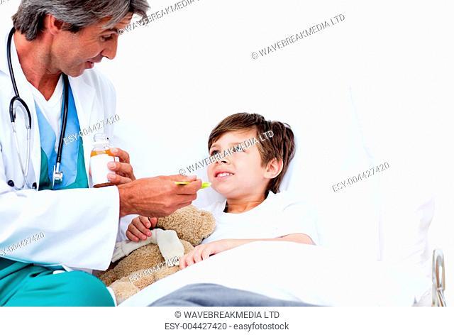Cute boy taking cough medicine