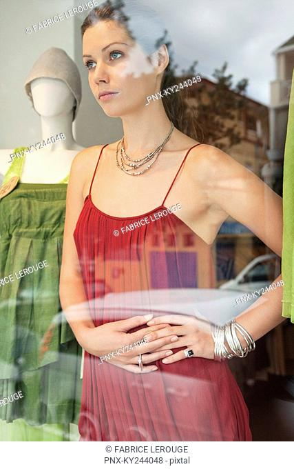 Woman imitating a mannequin in a boutique