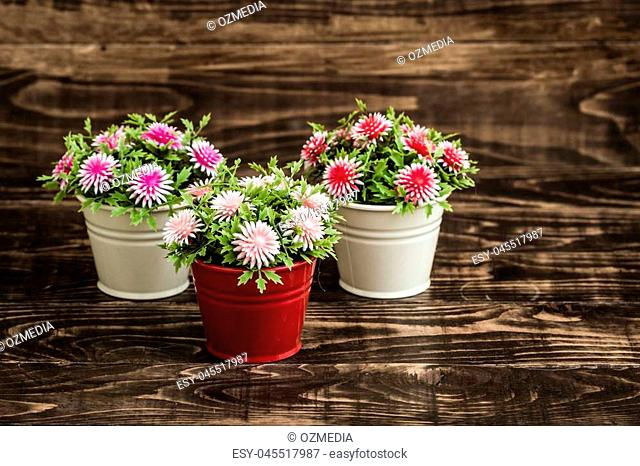 Artificial flowers in white flowerpots on brown wooden background