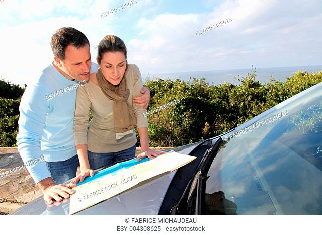 Couple looking at road map on car hood