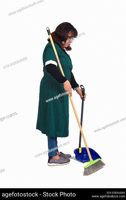 side view of a cleaning woman who is sweeping with a dustpan over white