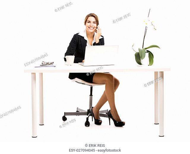 Happy business woman sitting on chair working with a tablet, isolated over white background