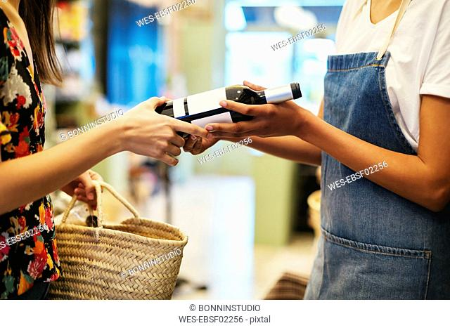 Shop assistant handing over wine bottle to customer in a store