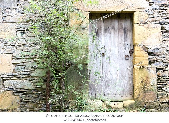 Old wooden door and stone wall. Agorregi, Pagoeta Natural Park, Basque Country, Spain
