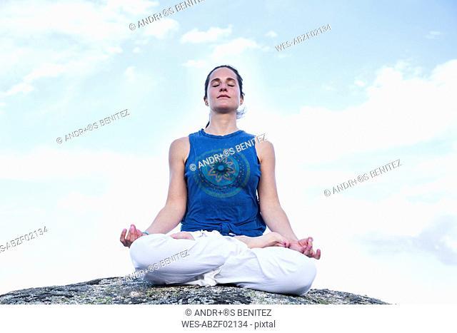 Woman doing yoga sitting on a rock