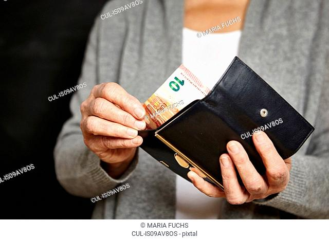 Woman getting money out of her wallet