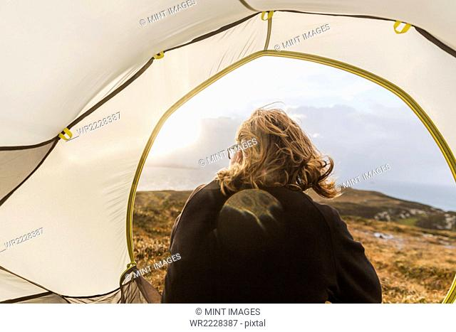 A man sitting in the shelter of a tent looking out