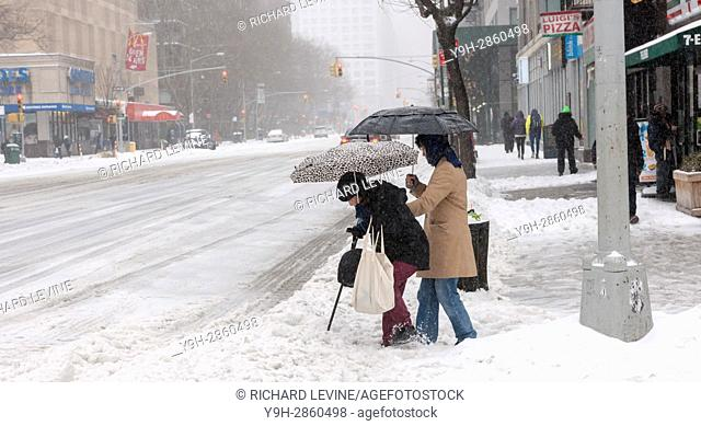 An elderly women is assisted in crossing Eighth Avenue through the snow in the Chelsea neighborhood of New York. Originally predicted as a blizzard with up to...