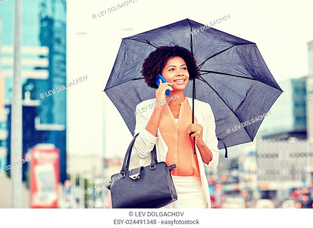 business, bad weather and people and concept - happy african american businesswoman with umbrella and handbag calling on smartphone at city street