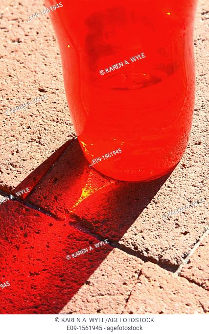 lower half of red water bottle with clear liquid inside casting red shadow, including bright streak inside shadow, on brownish-pink brick surface