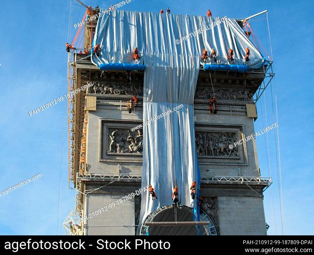 11 November 2021, France, Paris: Climbers have begun wrapping the Arc de Triomphe. The wrapping is to be completed by September 18