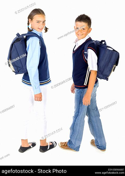 Portrait of boy and girl. They're looking at camera and smiling. Holding backpacks. Isolated on white in studio, side view