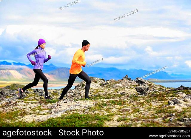 Running people trail runners in cross country run. Woman and man runners training jogging outdoors in beautiful mountain nature landscape on Snaefellsnes