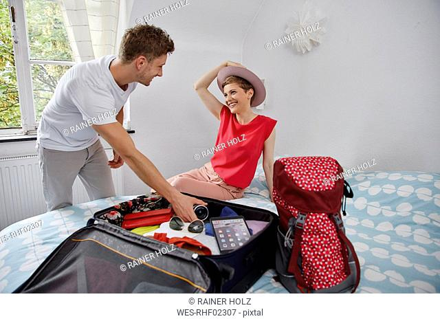 Happy couple packing suitcase for summer vacation on bed
