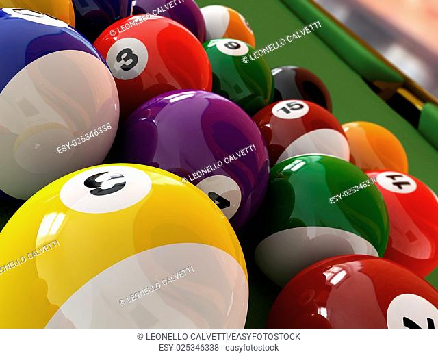 Group of billiard balls with numbers, on green pool table, with a hole in the background. Close up view