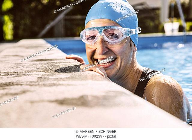 Female triathlete smiling happily at pool's edge