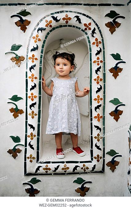 Thailand, Bangkok, Wat Arun, cute baby girl standing in a niche of the temple