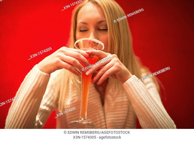 Woman drinking red cocktail