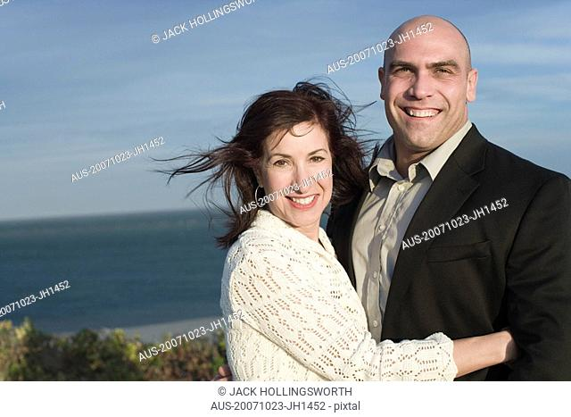 Portrait of a mature woman smiling with a mid adult man