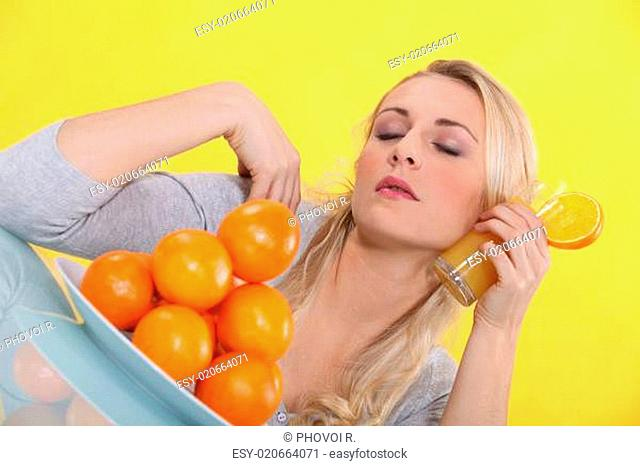 blonde woman refreshing his face with an orange juice glass