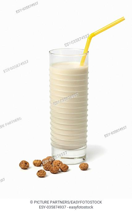 Glass Horchata milk and shelled chufa nuts on white background