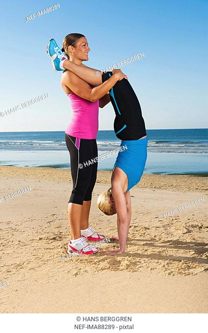 Two women exercising together on beach