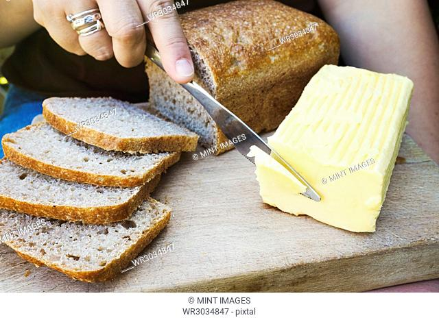 A person with a knife slicing through a block of butter for a sliced bread loaf