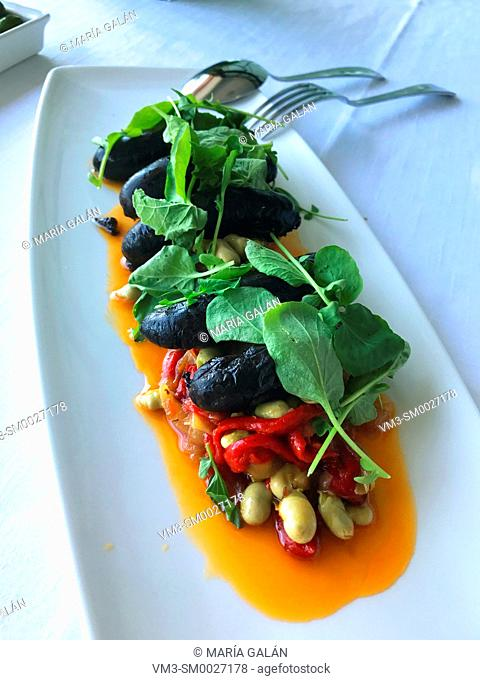 Salad made of beans, spinach leaves, morcillas and red peppers. Spain
